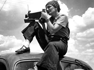 Dorothea Lange on top of car photographing migrants