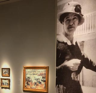 Large exhibition photo of E. Charton Fortune along side of some of her Cornwall paintings