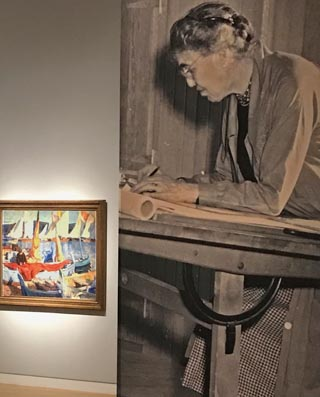 Large exhibition photo of E. Charlton Fortune at her drawing easel alongside her painting,  Drying Sails, St. Tropez